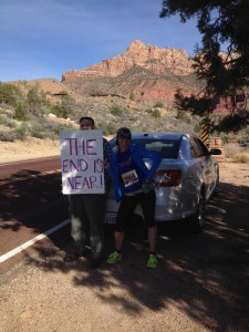 Spectators hold up funny signs to encourage runners at the Zion Half Marathon, Springdale, Utah, March 14, 2015 | Photo courtesy of Hollie Reina, St. George News
