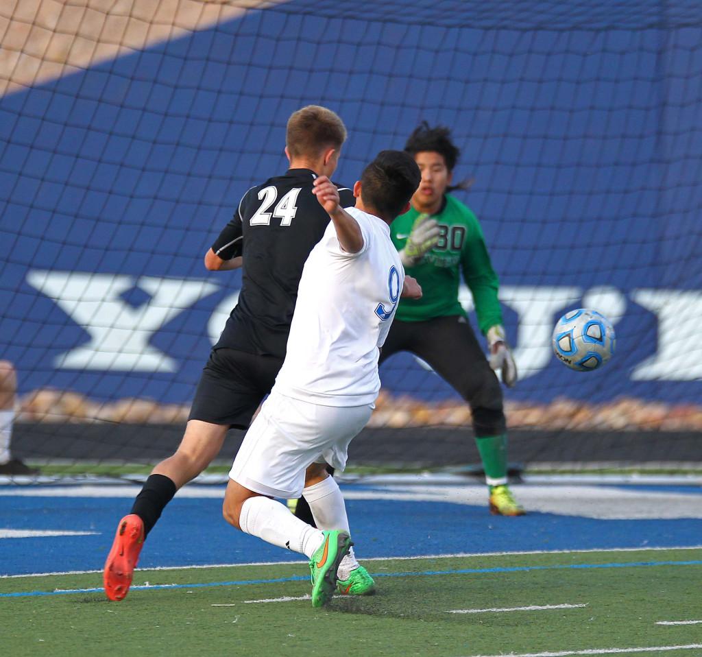 Dixie's Jonny Acosta (9) fires a shot on goal with Pine View's Easton Householder (24) defending, Pine View vs. Dixie, Soccer, St. George, Utah, Apr. 14, 2015 | Photo by Robert Hoppie, ASPpix.com, St. George News