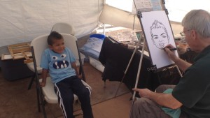 Bowie Klingonsmith, 4, sits while Oklahoma City artist Patrick Riley draws his portrait at the St. George Art Festival, St. George, Utah, April 3, 2015 | Photo by Holly Coombs, St. George News