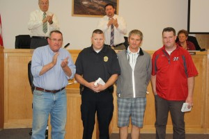 L - R Mayor John Bramall and the city council applaud Officer Spence Lundell, Jared Elison, and Bryce King for helping an 11-year-old visitor replace his stolen baseball equipment, Hurricane City Council, Hurricane, Utah, April 16, 2015 | Reuben Wadsworth, St. George News