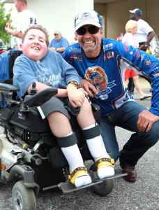 Kyle Petty smiles with young boy involved in Victory Junction camp, location and date unspecified | Photo courtesy of the Kyle Petty Charity Ride, St. George News