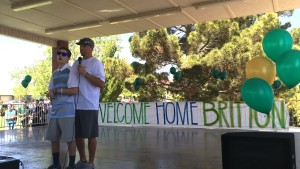 Britton Shipp and his father, Jesse Shipp, and the stage address the crowd gathered to welcome Britton home after over 160 days in the hospital, Santa Clara, April 11, 2015 | Photo by Mori Kessler, St. George News
