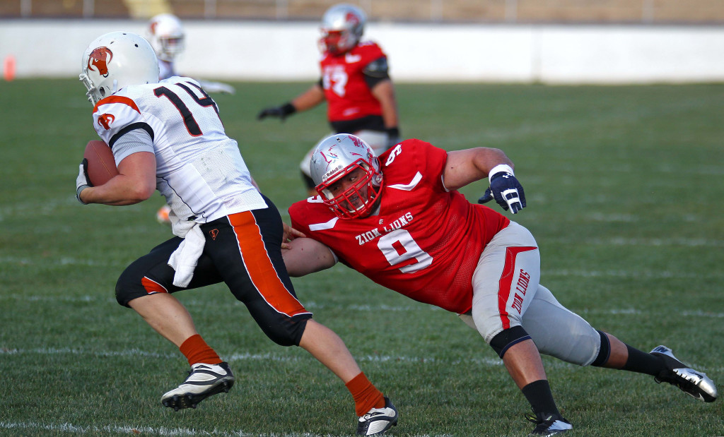 Zion defensive end Vince Feula (9) brings down the Logan quarterback for a loss, Logan Stampede vs. Zion Lions, Football, St. George, Utah, May 2, 2015 | Photo by Robert Hoppie, ASPpix.com, St. George News