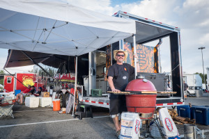 "Scott ""Manno""Manning, from Fort Collins, Colorado,  poses next to his barbecue equipment outside his trailer."