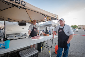 Wayne Hoppal (left) and Ken Thompson (right), both from St. George, prepare a slab of meat at their station.