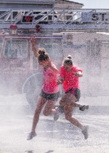Racers run through the spray of a fire truck hose, location and date not specified | Photo by Dave Becker courtesy of Fire Hose Frenzy, St. George News