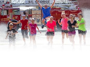 Racers run through the spray of a fire truck hose, location and date not specified   Photo courtesy of Fire Hose Frenzy, St. George News