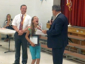 L-R Sunset Elementary principal Anthony Horrocks looks on as student Annabel Smith receives a $100 check and certificate from Mayor Jon Pike Friday May 1, 2015 | Photo by Ric Wayman, St. George News