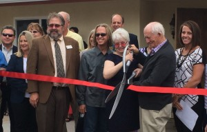 Sue and Ron Kimball – couple holding the giant scissors – cut the ribbon signifying the official opening of the newest transition home the Erin Kimball Foundation has established in the community for survivors of domestic violence and sexual assault, Washington City, Utah, May 7, 2015 | Photo by Mori Kessler, St. George News