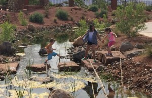 Right to left) 7-year-old Maxwell Kearl, along with 10-year-old Annabella Blackmer and 3-year-old Mia Blackmer, crossing the steam at the Red Hills Desert Garden, St. George, Utah, May 20, 2015 | Photo By Mori Kessler, St. George News