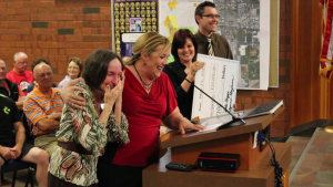 Debbie Justice (left, foreground) gets a surprise at the City Council meeting once she's told the sensory  garden at the All Abilities Park will be named after her, St. George, Utah, May 21, 2015 | Photo by Mori Kessler, St. George News