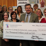 L-R: Debbie Justice at far left of the giant check; St. George Mayor Jon Pike stands in center behind the check; Shirlee Draper at far right of giant check; amidst members of The Learning Center for Families board of directors and others. The check represents TLC's $10,000 donation toward the All Abilities Park's sensory garden. City Council Chambers, St. George, Utah, May 21, 2015 | Photo by Mori Kessler, St. George News
