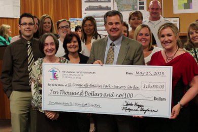 L-R: Debbie Justice at far left of the giant check; St. George Mayor Jon Pike stands in center behind the check; Shirlee Draper at far right of giant check; amidst members of The Learning Center for Families board of directors and others. The check represents TLC's $10,000 donation toward the All Abilities Park's sensory garden. City Council Chambers, St. George, Utah, May 21, 2015   Photo by Mori Kessler, St. George News