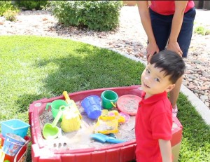 Enoch Neaville smiles for the camera while playing with a sandbox, St. George, Utah, June 6, 2015   Photo by Nataly Burdick, St. George News