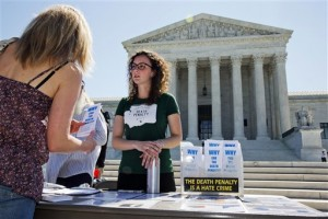 "Danielle Fulfs, 24, of Seattle, with the Washington Coalition to Abolish the Death Penalty, hands out materials about the death penalty outside of the Supreme Court in Washington, Monday June 29, 2015. A deeply divided Supreme Court upheld the use of a controversial drug in lethal-injection executions Monday, even as two dissenting justices said for the first time they think it's ""highly likely"" the death penalty itself is unconstitutional 