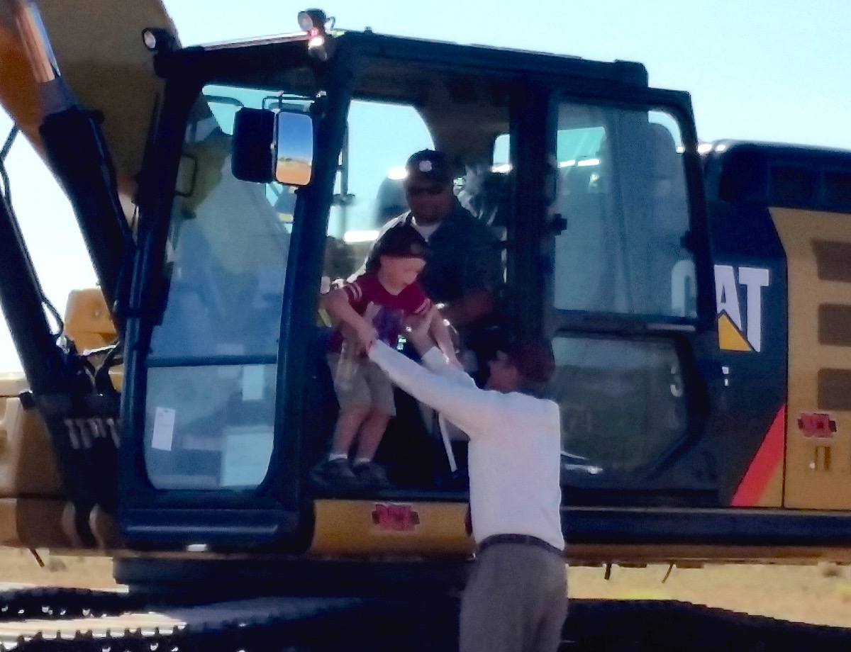 Bob Harmon lifts his grandson from a trackhoe during a groundbreaking ceremony Monday for a new Harmons grocery store, Santa Clara, Utah, June 22, 2015 | Photo by Julie Applegate, St. George News