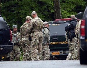 Law enforcement officers gather on a road on Sunday, June 28, 2015, in Malone, N.Y. The shooting death of one escaped killer brought new energy to the three-week hunt for a second escaped murderer in the United States as helicopters, search dogs and hundreds of law enforcement officers converged on a wooded area 30 miles from Clinton Correctional Facility| Photo by  AP Mike Groll, St. George News