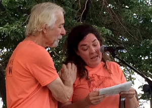 Groovefest Music and Art festival founder Tim Cretsinger places a reassuring hand on his wife Lisa Cretsinger's shoulder as she breaks down while reading his message to the crowd, Main Street Park, Cedar City, Utah, June 27, 2015 | Photo by Carin Miller, St. George News