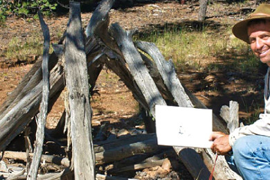 Archaeologist Neil Weintraub kneels next to a brush shelter discovered on Kaibab National Forest, Williams, Arizona, undated | Photo courtesy of United States Forest Service, St. George News