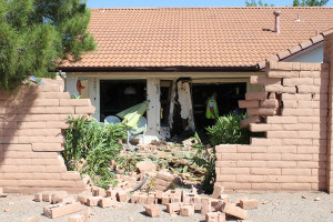 Damage to a brick wall and house after a Suzuki SX4 crashed into them, St. George, Utah, June 2, 2015 | Photo by Nataly Burdick, St. George News