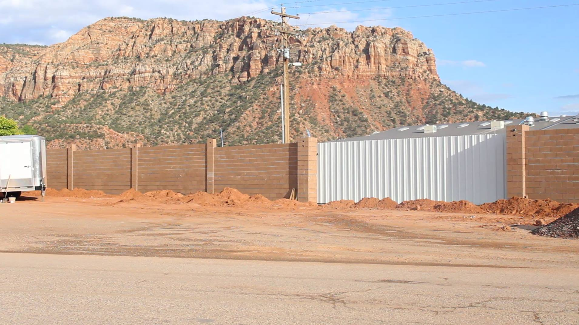 Left: Wall appears to be complete on July 4 surrounding the Leroy S. Johnson meeting house of the FLDS Church, built without explanation to the public during the week of July 1, some say in response to a Short Creek community 4th of July celebration. Colorado City, Arizona, July 4, 2015 | Photo by Nataly Burdick, St. George News
