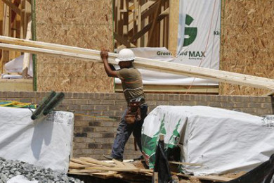 In this photo, a worker carries a load of lumber at a new home construction site in Mechanicsville, Va. The Commerce Department reports on home construction during June on Friday, July 17, 2015, Mechainicsville, Va., June 8, 2015 | AP Photo by Steve Helber, St. George News