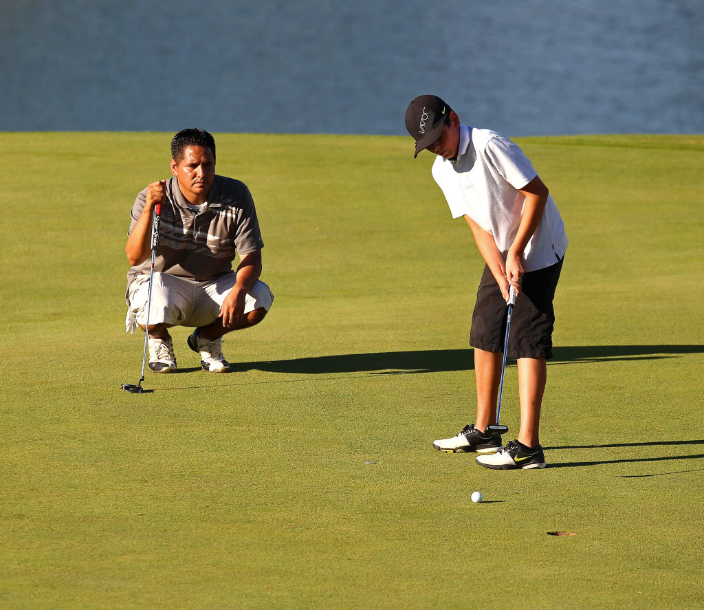 Jace Lee putts as his father Scott Lee watches, City of St. George JAG summer golf tournament, St. George, Utah, July 16, 2015, | Photo by Robert Hoppie, ASPpix.com, St. George News