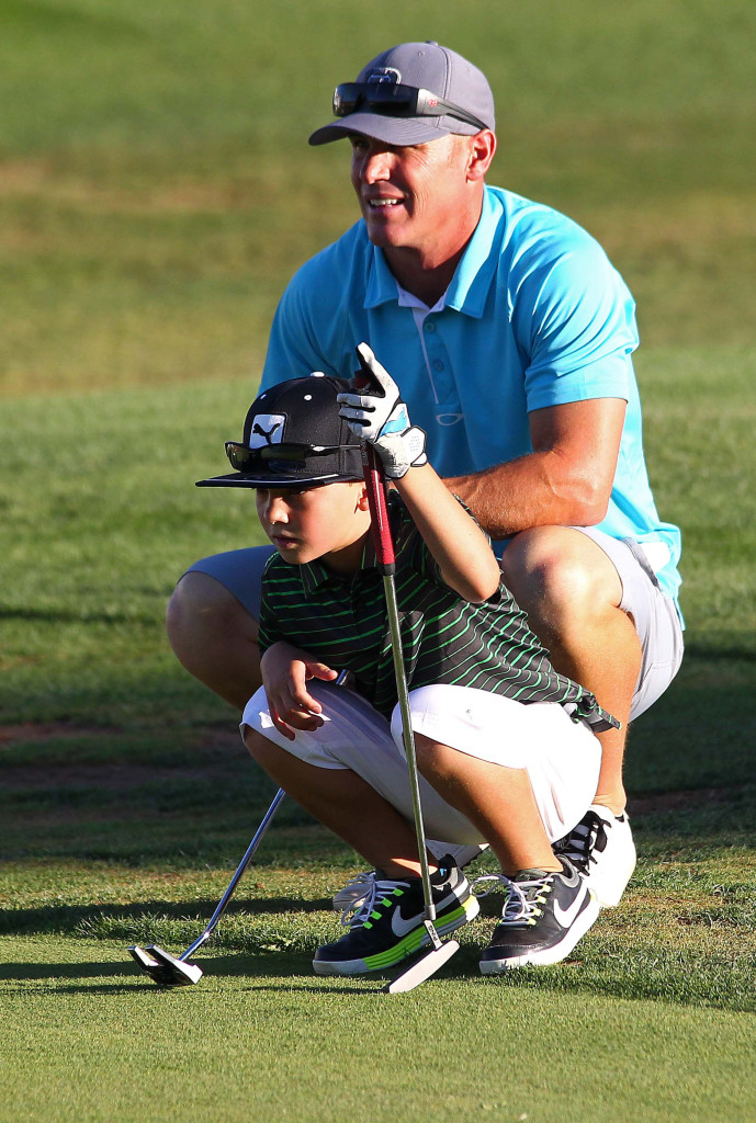 Ryan Filmore and his son Jace Filmore study the ninth green before putting, City of St. George JAG summer golf tournament, St. George, Utah, July 16, 2015, | Photo by Robert Hoppie, ASPpix.com, St. George News