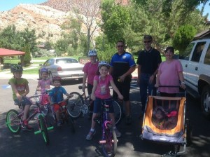 """The Blodgett family, of Cedar City, were the first recipients of this year's """"Playin' Safe"""" gift cards. The Blodgetts were caught by Cedar City Police officers while preparing for a bicycle ride at Cedar City's Canyon Park. Each of the Blodgetts were practicing bicycle safety by wearing their bicycle helmets. Their safe act was rewarded by CCPD Officer Travis Carter, who issued each of the kids a Subway gift card. Cedar City, Utah, July 28, 2015 