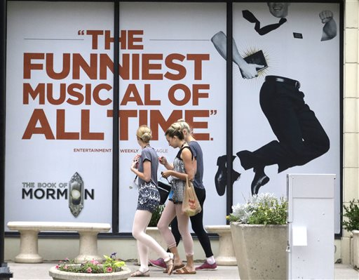 "People walk past signs announcing the ""Book of Mormon"" musical at the Capitol Theatre, Monday, July 27, 2015, in Salt Lake City. The biting satirical musical that mocks Mormons is finally coming to the heart of Mormonlandia, starting a sold-out, two week run on Tuesday, July 28, 2015, at a theater two blocks from the church's flagship temple and headquarters, Salt Lake City, Utah, July 27, 2015 