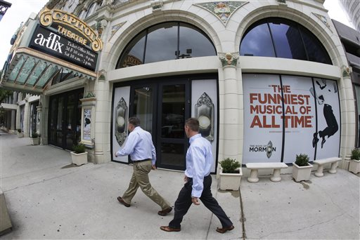 """People walk past signs announcing the """"Book of Mormon"""" musical at the Capitol Theatre, Monday, July 27, 2015, in Salt Lake City. The biting satirical musical that mocks Mormons is finally coming to the heart of Mormonlandia, starting a sold-out, two week run on Tuesday, July 28, 2015, at a theater two blocks from the church's flagship temple and headquarters, Salt Lake City, Utah, July 27, 2015 
