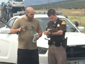 Alex Caballero, the driver of Semitrailer involved in a vehicle fire on northbound I-15 at milepost 48, discusses the details of the accident with Utah Highway Patrol Trooper Nathan Clark, Kanarravile, Utah, July 3, 2015 | Photo by Carin Miller, St. George News