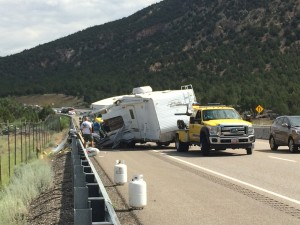 A tow truck prepares to tow away the remains of a trailer that flipped on I-15, spilling it's contents into the roadway, Washington County, milepost 36, July 6, 2015 | Photo by Devan Chavez, St. George News
