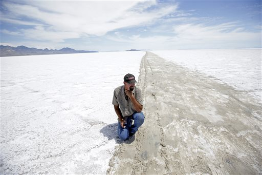 In this photo, Wendover Mayor Mike Crawford kneels down along the exposed mud track on the Bonneville Salt Flats in Utah. Crawford, who owns an auto parts shop in town, said the decision by race organizers to cancel this year's event weeks away will be a bigger economic blow than last year, when a monsoon storm left standing water on the track on the eve of the race. Wet weather has forced the second-straight cancellation of an annual race at Utah's world-famous Bonneville Salt Flats, Wendover, Utah, July 21, 2015 | AP Photo by Rick Bowmer, St. George News