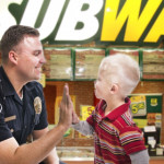Firefighter gives young boy a high five | Stock image, St. George News