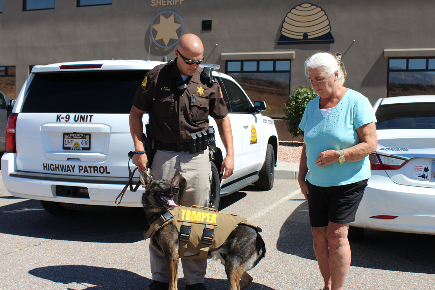 L-R: UHP Trooper Chris Terry and K-9 Titan meet Margaret Manazer, who donated a stab and bulletproof vest for Titan;  in front of UHP Section 12 Office, Hurricane, Utah, July 25, 2015 | Photo by Nataly Burdick, St. George News