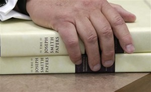The Church of Jesus Christ of Latter-day Saints historian Steven E. Snow rests his hand on the third volume of the Joseph Smith papers, which includes the printer's manuscript of the Book of Mormon, during a news conference, Salt Lake City, Utah, Aug. 4, 2015 | AP Photo by Rick Bowmer, St. George News