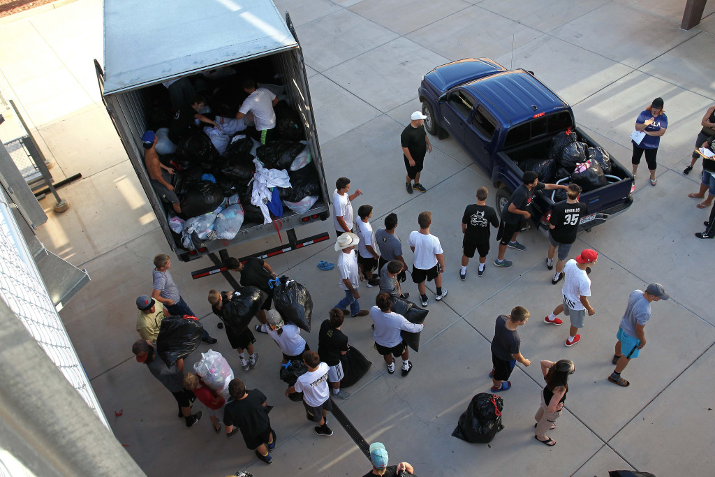 Players from the Desert Hills Football team load bags of donated clothes into a semi-truck to be taken to the I Won't Cheat Foundation, Desert Hills Football Charity Fundraiser, St. George, Utah, Aug. 15, 2015, | Photo by Robert Hoppie, ASPpix.com, St. George News