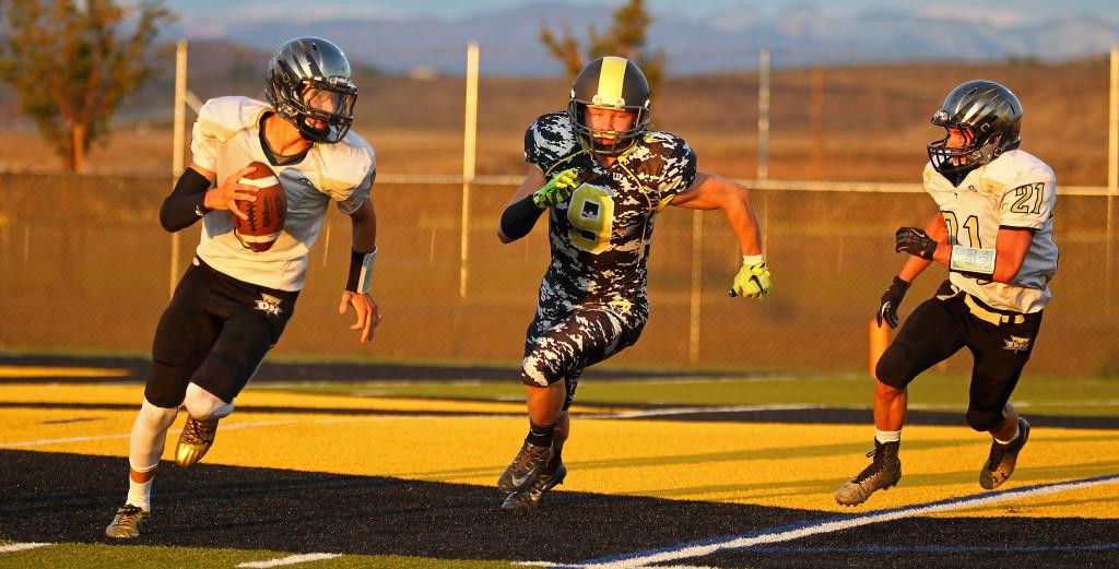 Diamond Ranch defensive back Corey Tullen (9) in pursuit of the Desert Hills quarterback Kobe SattiewhiteDiamond Ranch Academy vs. Desert Hills JV, Football, Hurricane, Utah, Aug. 27, 2015, | Photo by Robert Hoppie, ASPpix.com, St. George News