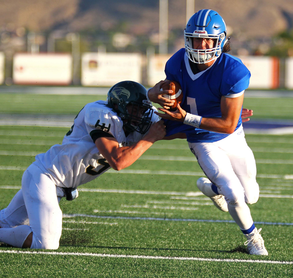 Dixie quarterback Zac Harrah (1) eludes a Mohave tackler, Dixie vs. Mohave Ariz. Football, St. George, Utah, Aug. 28, 2015, | Photo by Robert Hoppie, ASPpix.com, St. George News