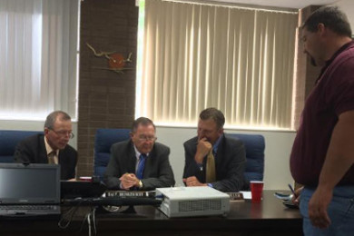 Iron County Commissioners (L-R) Alma Adams, Dale Brinkerhoff and David Miller gaze down at some building plans while the lead maintenance worker Lester Ross goes over their possible options, Parowan, Utah, Aug. 24, 2015 | Photo by Devan Chavez, St. George News
