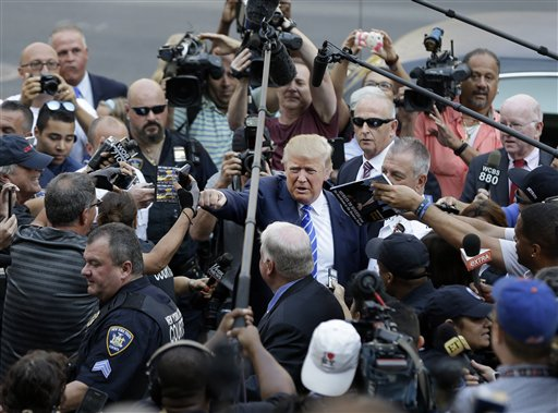 Donald Trump, center, gives a fist bump to a pedestrian as he arrives for jury duty in New York, Monday, Aug. 17, 2015. Trump was due to report for jury duty Monday in Manhattan. The front-runner said last week before a rally in New Hampshire that he would willingly take a break from the campaign trail to answer the summons. AP Photo by Seth Wenig, St. George News