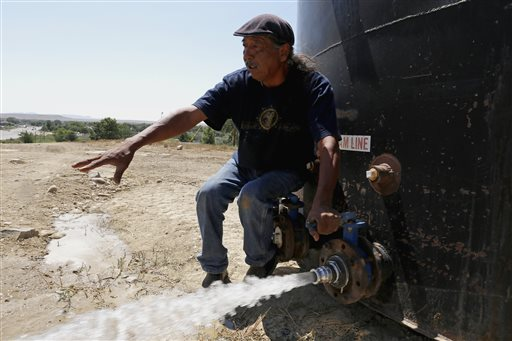 In this Aug. 18, 2015, photo, Joe Ben Jr., Shiprock Chapter House Farm Board representative, tests the water from tanks at the Chief Hill location in Shiprock, New Mexico. The quality of San Juan River water on the Navajo Nation has returned to what it was before a spill at a Colorado gold mine sent toxic sludge into the waterway, federal officials said Thursday. Shiprock, News Mexico, Aug. 18, 2015 | Photo by Alexa Rogals/The Daily Times via AP; St. George News