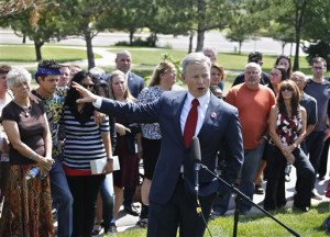 District Attorney George Brauchler, backed by the families of those killed and wounded, speaks with members of the media after Colorado movie theater shooter James Holmes was formally sentenced, outside Arapahoe County District Court. Holmes was sentenced to multiple life sentences without parole for perpetrating the July 20, 2012 attack that left 12 dead and 70 wounded, Centennial, Colo., Aug. 26, 2015 | AP Photo by Brennan Linsley, St. George News