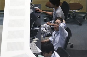 A worker of Tokyo Stock Exchange monitors stock prices on an electric screen during a trading session in Tokyo, Monday. Stocks tumbled across Asia on Monday as investors shaken by the sell-off last week on Wall Street unloaded shares in practically every sector, Tokyo, Japan, Aug. 24, 2015 | AP Photo by Koji Sasahara, St. George News