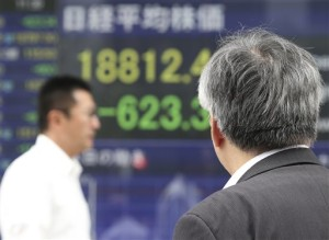 A man looks at an electronic stock board of a securities firm in Tokyo, Monday. Stocks fell in early trading Monday in Asia as investors shaken by the sell-off last week on Wall Street unloaded shares in many sectors, Tokyo, Japan, Aug. 24, 2015 | AP Photo by Koji Sasahara, St. George News