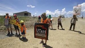Protesters gather outside the U.S. Oil Sands commercial tar sands operation, in the Book Cliffs, in eastern Utah. On a remote Utah ridge covered in sagebrush, pines and wild grasses, a Canadian company is about to embark on something never before done commercially in the United States: digging sticky, black, tar-soaked sand from the ground and extracting the petroleum, Black Cliffs, Utah, July 13, 2015 | AP Photo by Rick Bowmer, St. George News