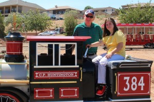 Amber Graves (sitting on the engine) and Kent Perkins, St. George Leisure Services Director, pose for photos, St. George, Utah, Aug. 17, 2015   Photo by Mori Kessler, St. George News