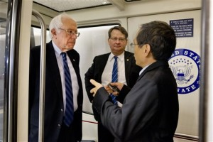 Democratic presidential candidate Sen. Bernie Sanders, I-Vt., left, is interviewed as he leaves after a Senate vote on Capitol Hill to approved a stopgap spending bill to avert a government shutdown. Sen. Gary Peters, D-Mich. is at center, Capitol Hill, Washington, Sept. 30, 2015 | AP Photo by Jacquelyn Martin, St. George News