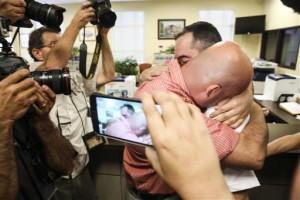 James Yates, right, hugs his partner William Smith Jr., after receiving their marriage license at the Rowan County Judicial Center. Deputy clerk Brian Mason issued the license, congratulating the couple and shaking their hands as he smiled, Morehead, Ky, Sept. 4, 2015 | AP Photo by Alton Strupp, The Courier-Journal, St. George News